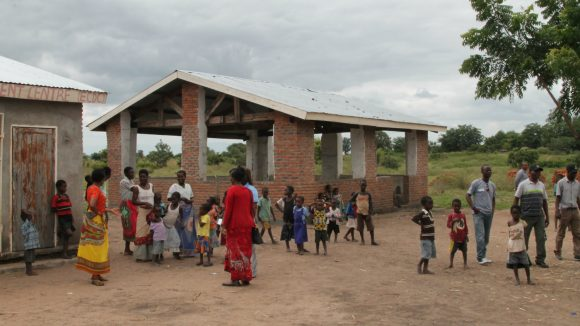 Adults and children in Malawi attend a project where a school is being built.