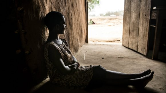 A Uganda woman with a physical disability sits alone in her house.