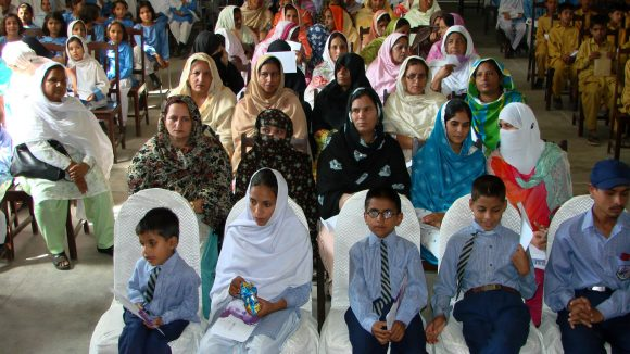 Teachers, workers and children gather for a seminar for World Sight Day in Pakistan.