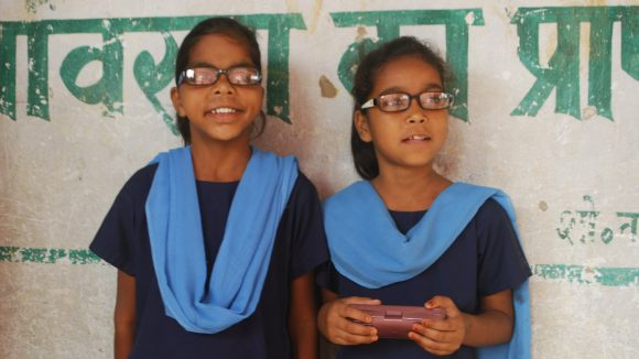 Two young sisters who wear glasses attend school in India.