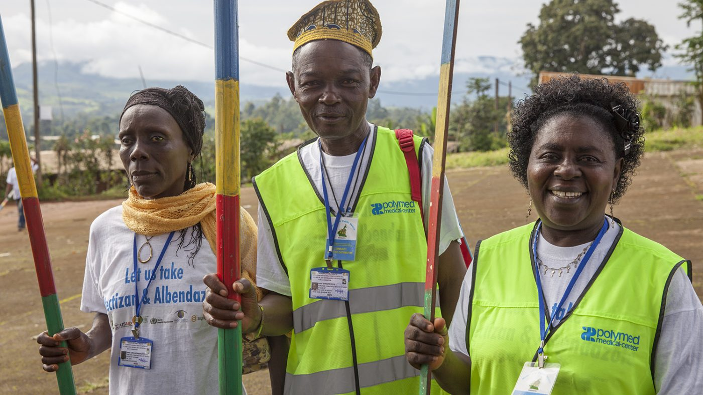 Two women and a man are carrying measuring sticks to calculate the dosage of Mectizan. Two of them are wearing high-vis tops.
