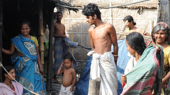 A group of people standing in a slum area in Dhaka.
