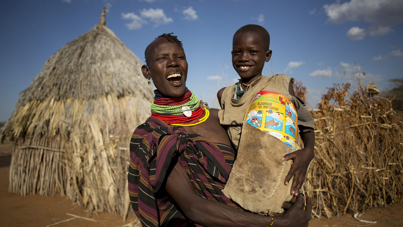 A woman holding a child, smiling and standing outside a thatched dwelling.