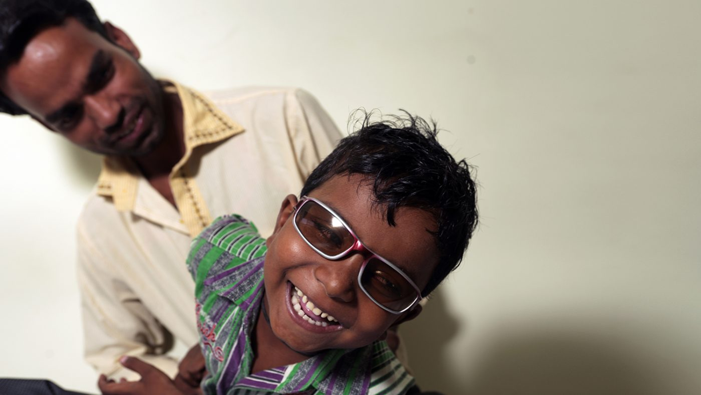 A young boy wearing dark glasses, laughing.