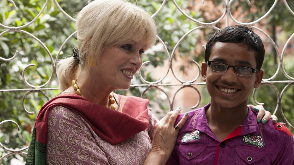 Joanna Lumley stands besides Arif, outside infront of green plants.