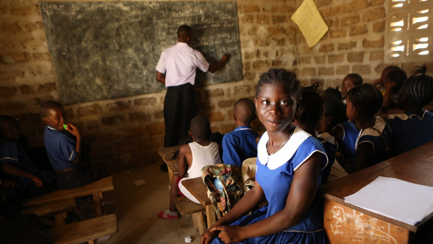 A young girl sitting in a classroom.