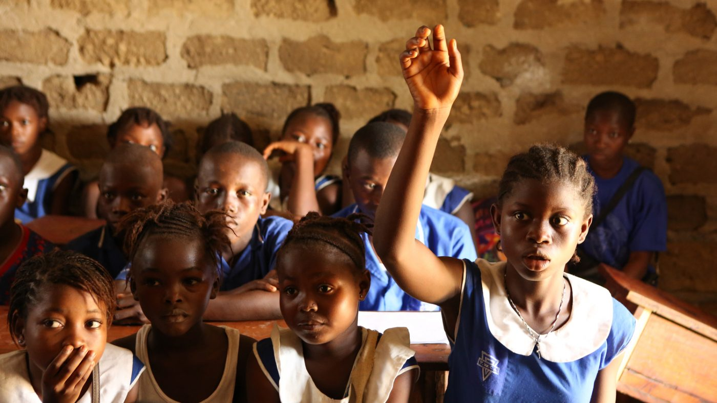 A young girl raising her hand in a busy classroom.
