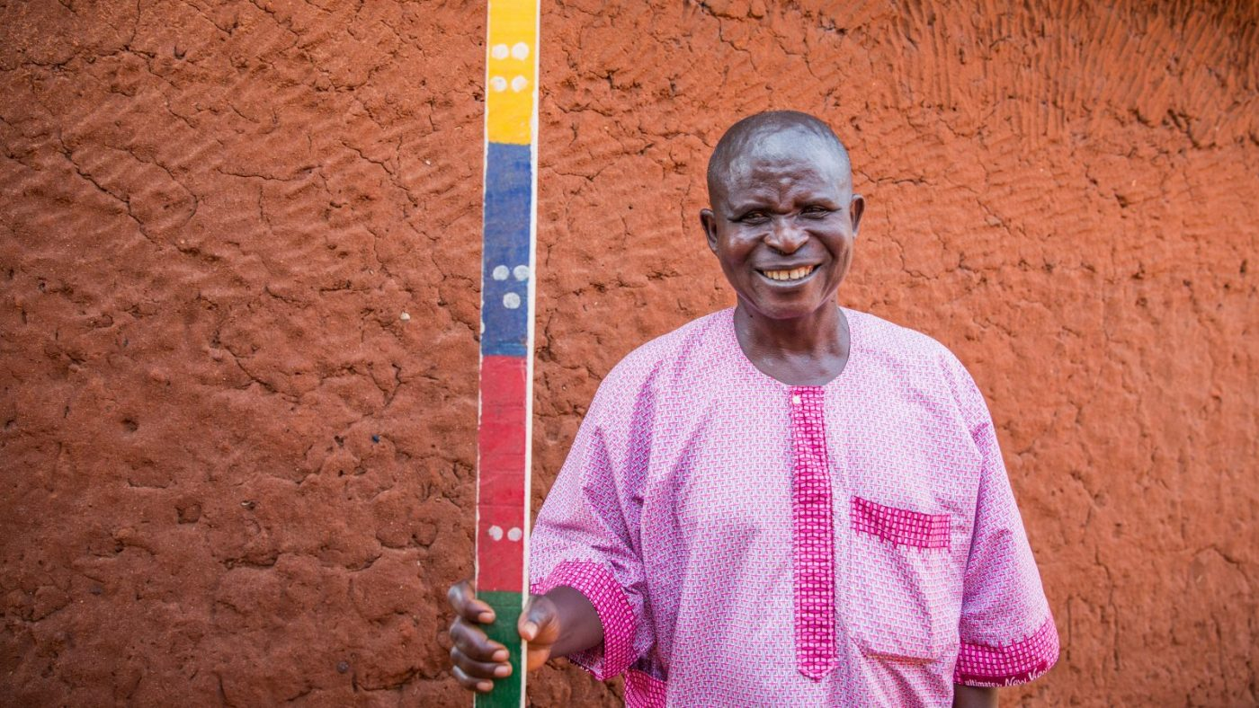 A man standing next to a long stick used for determining medicine doses.
