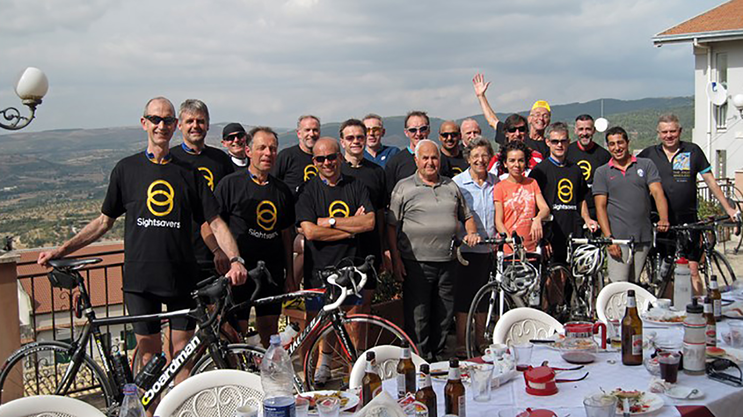Members of the Jolly Wheelers cycle group wearing Sightsavers t-shirts, standing with their bicycles outside a restaurant high on a hill in Italy.