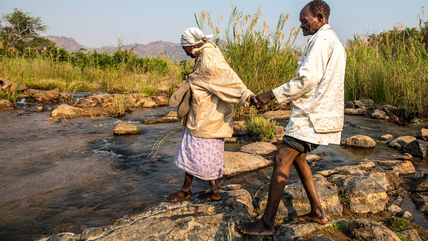 Winesi being guided across a river by his wife.