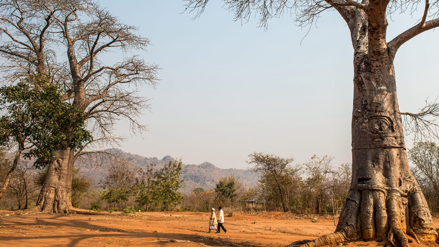 Winesi walks with his wife in his village.