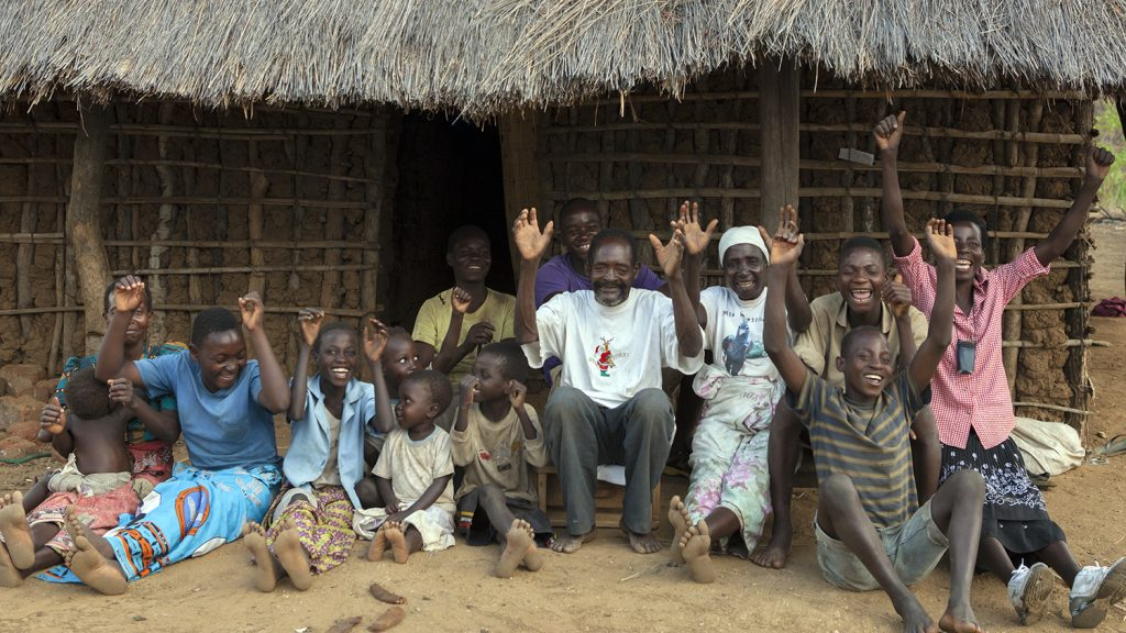 Winesi and his extended family cheering outside a house.