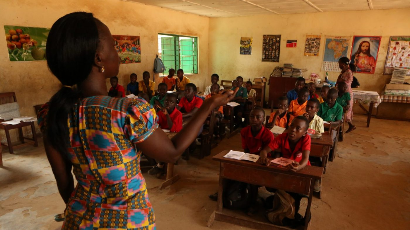 A female teacher is standing at the front of a classroom teaching, many school children are looking at her.