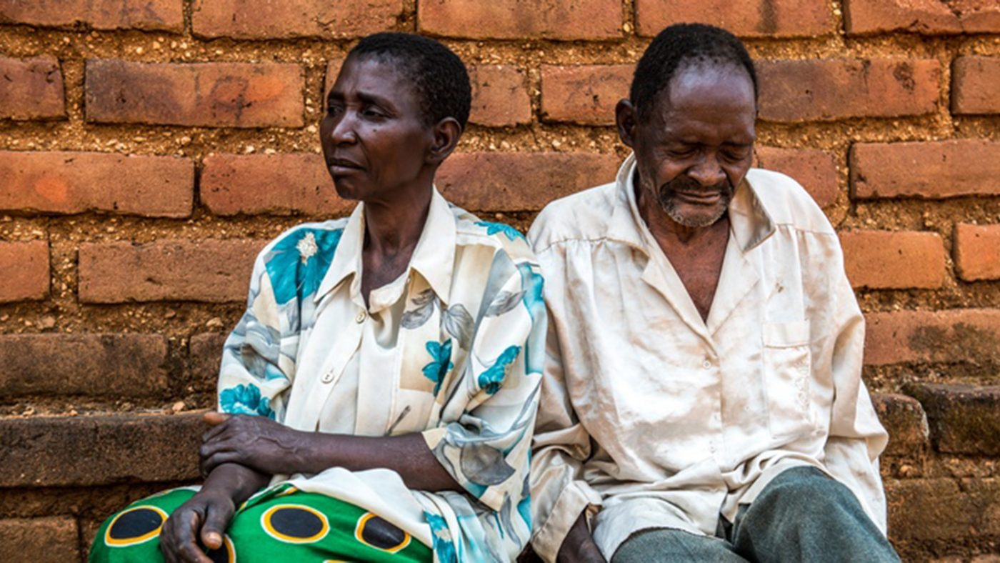 Winesi, who has cataracts, sits outside his home in Malawi with his wife Namaleta.