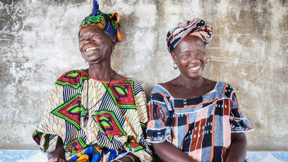 Sisters Awa and Arame Ndiaye sit next to each other, both of them are smiling.