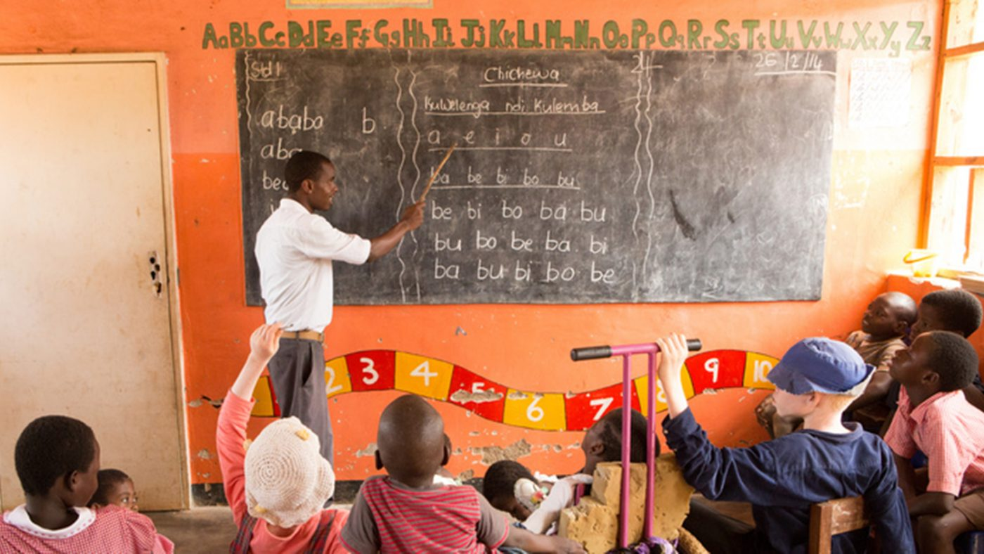 A teacher writing on a blackboard in front of a group of children.