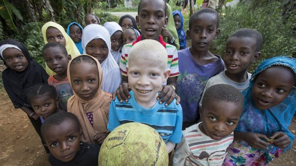 Rajab Abdawa (10), holds a ball and is surrounded by other children..