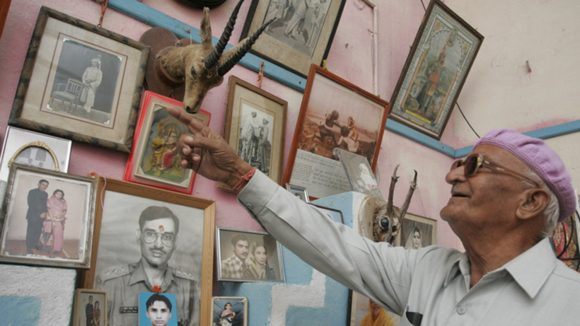 A older man is looking a wall, with lots of photographs of family on it. He is pointing to one photograph and smiling.