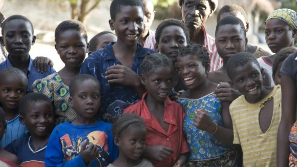 A group of smiling children are standing next to each other.