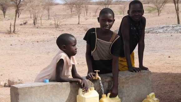 Three children lean over a wall and fill yellow containers with water from a tap.