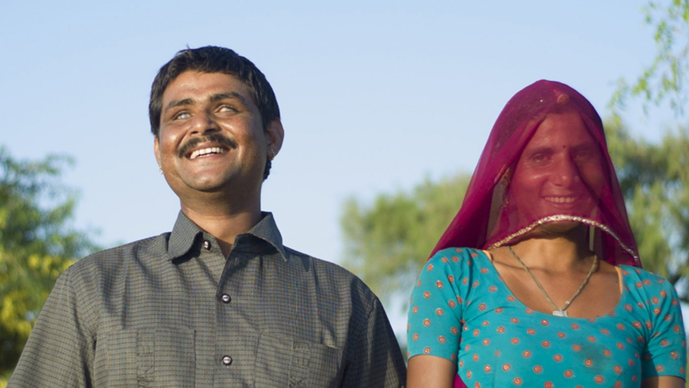 A visually impaired man and a woman holding hands as they walk outside.