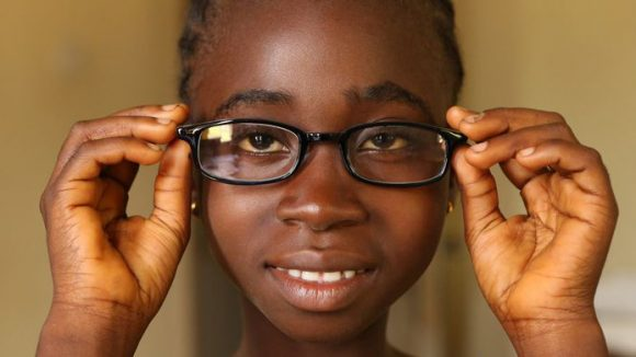 A girl holds her glasses up to her face and looks at the camera.