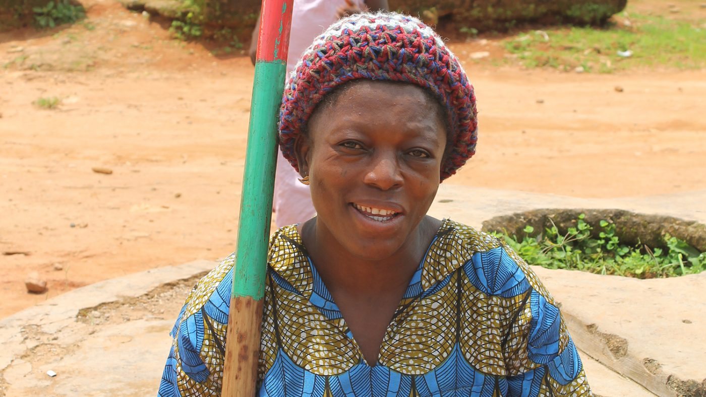 Close up of a woman smiling sitting outside.