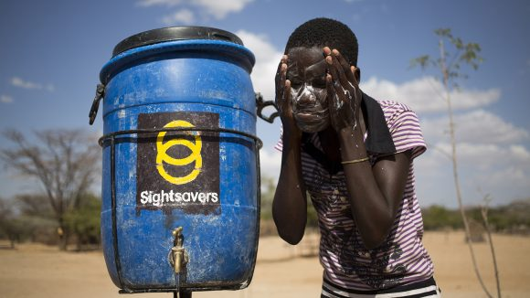 A young girl leans over a barrel of water, with Sightsavers' logo on it. She is washing her face outside with soapy water.