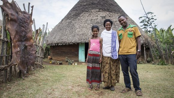 Two adults and a young female stand infront of a house.