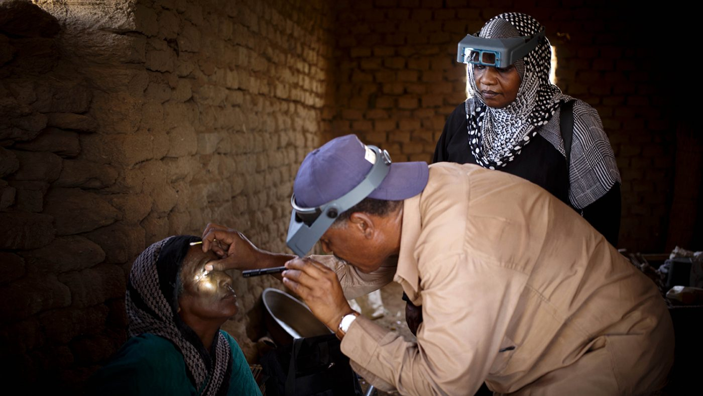 Dr Bilghis monitors a grader as they examine a woman's eyes for trachoma in a village near Khartoum, Sudan.