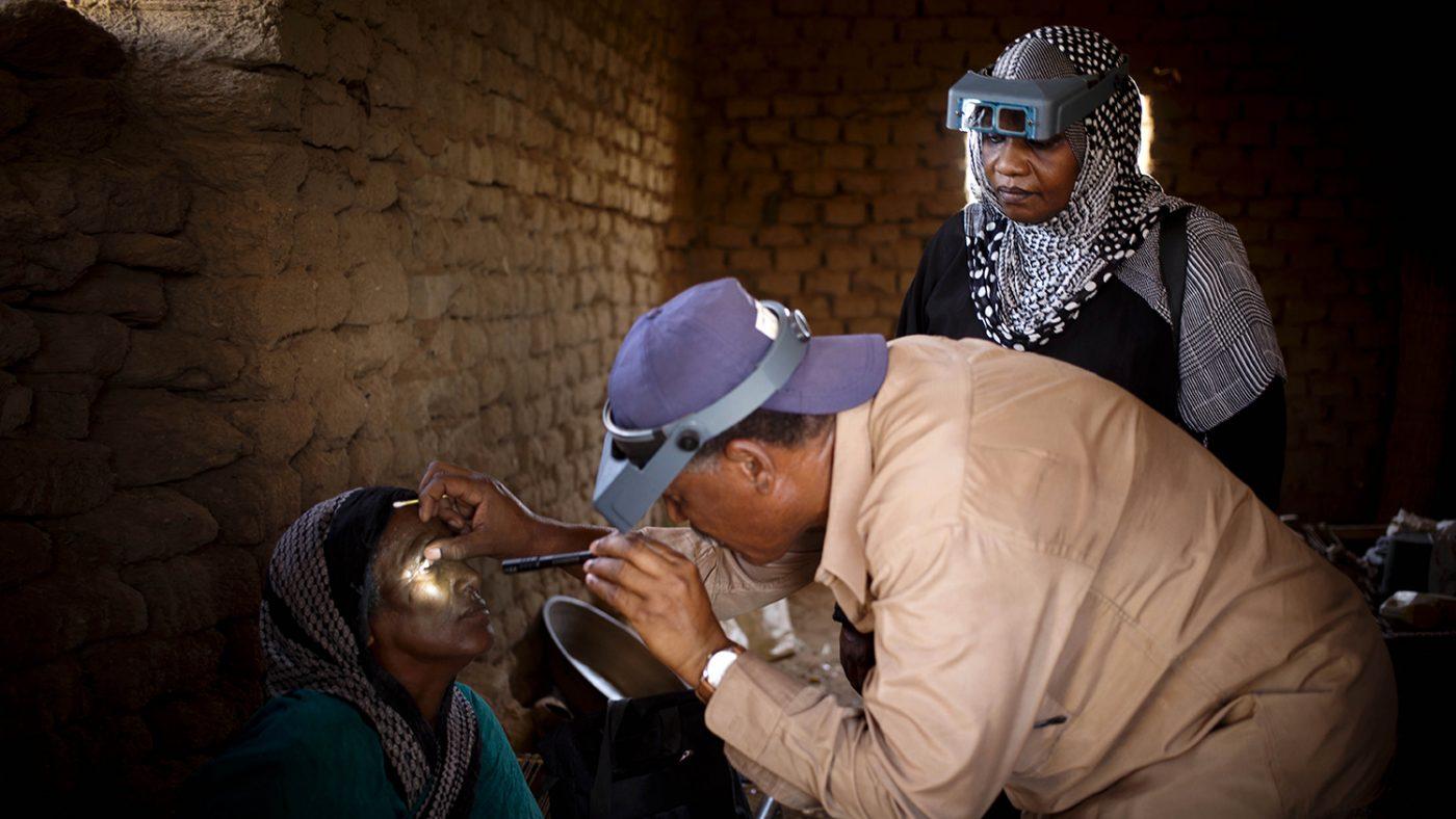 Dr Bilghis monitors a grader as they examine a woman's eyes for trachoma in a village near Khartoum, Sudan.