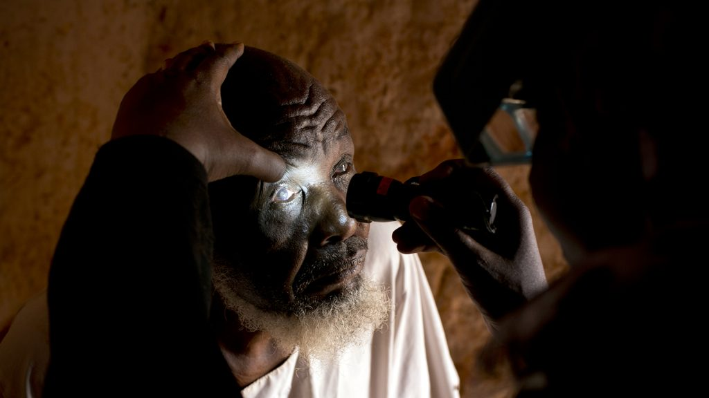A close-up view of Dr Bilghis examining 82-year-old Issa Dawood, who has trachoma., by shining a light into his eye.