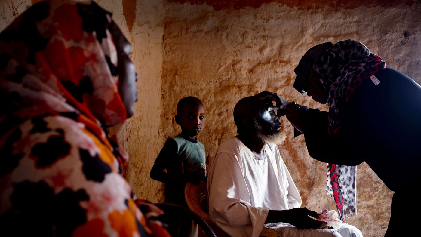 Dr Bilghis examines 82-year-old Issa Dawood, who has trachoma., by shining a light into his eye.