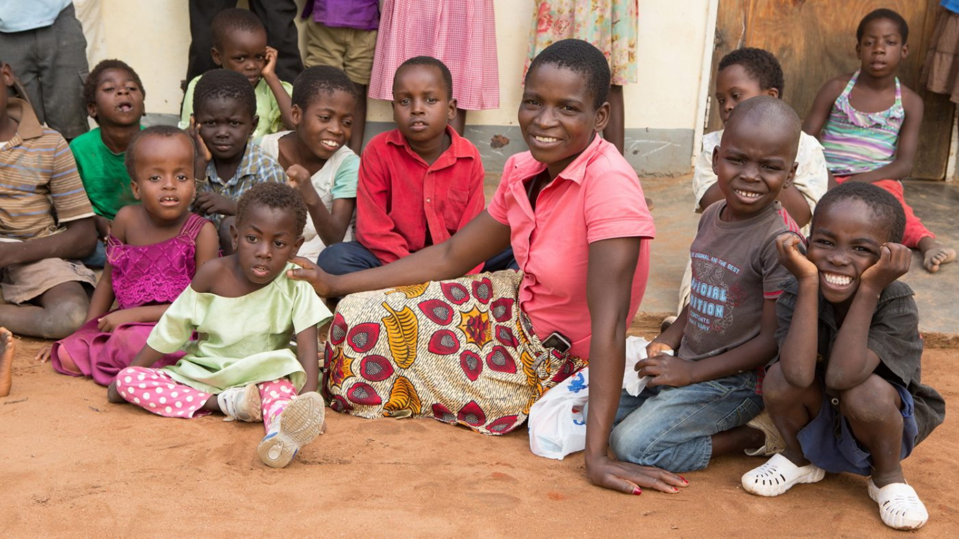 A lady named Miriam sits on the ground outside in Malawi, with the children of the Dawn Centre around her.