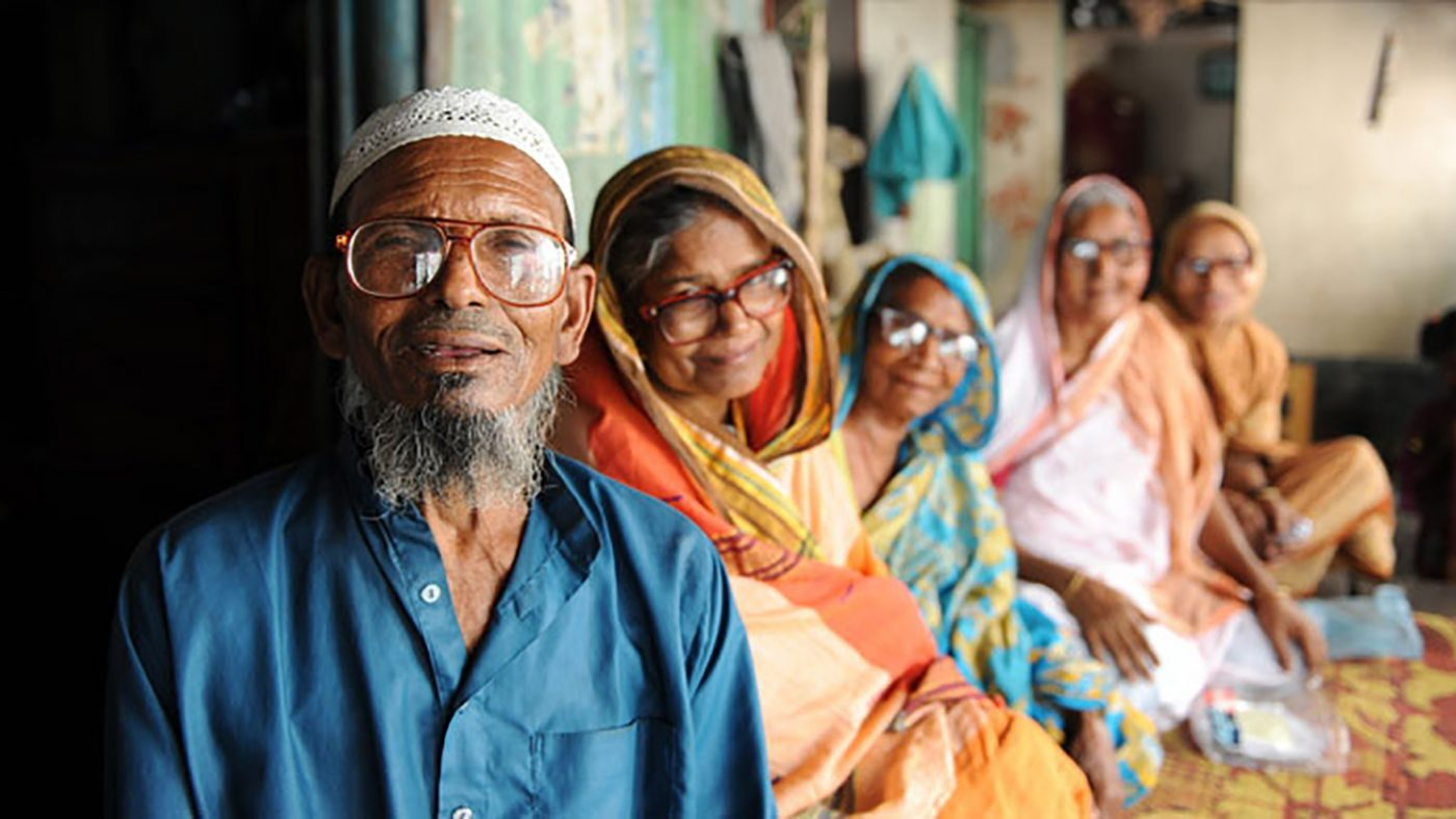 A group of five elderly people on Bhopal. All are sitting on the floor smiling, while wearing spectacles.