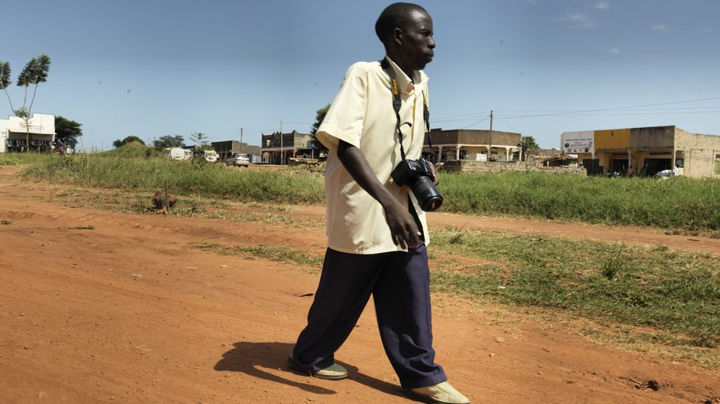 Rajab walking along a dirt path with his camera around his neck.