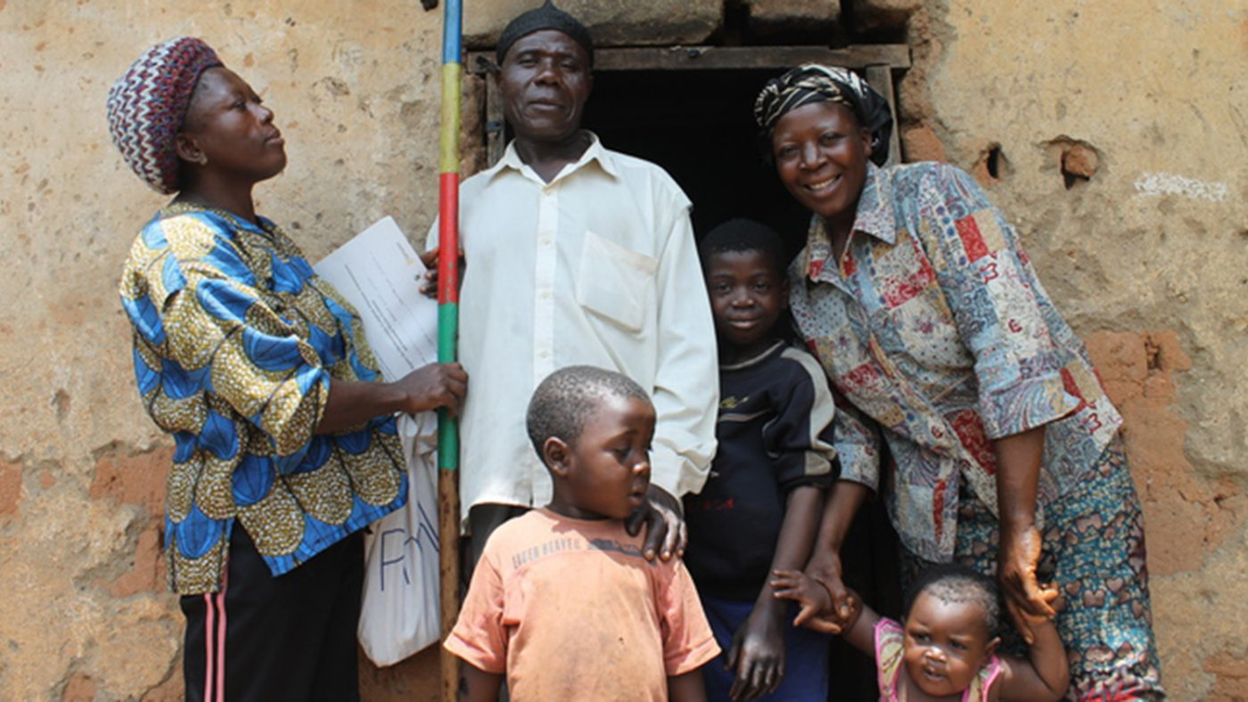 A woman holding a measuring stick to determine treatment dosage, standing next to a family.