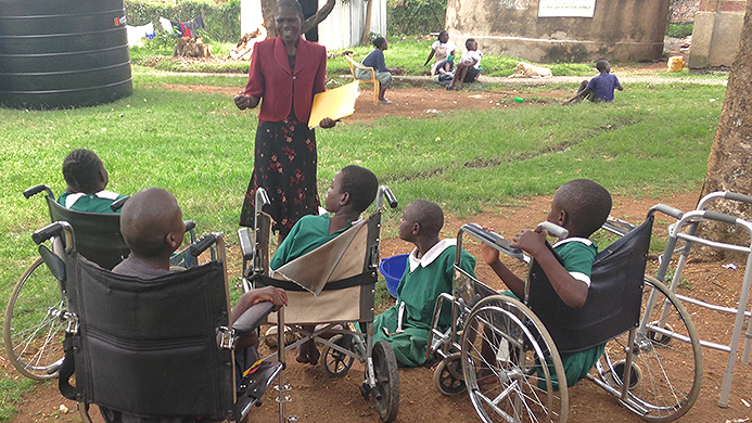 An adult standing in front of a group of young students who are wheelchair users.