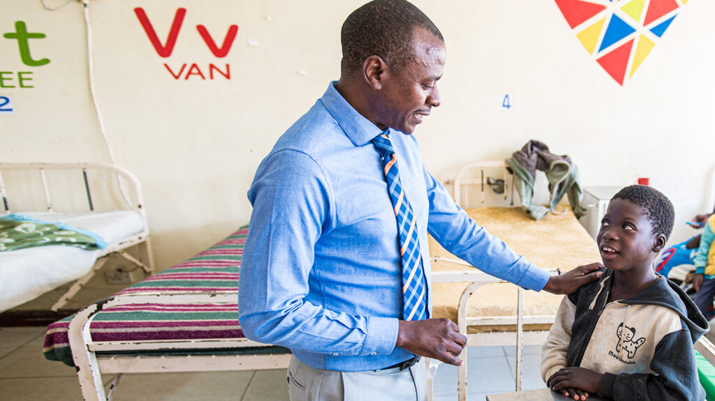Dr Msukwa puts his hand on the shoulder of a young patient.