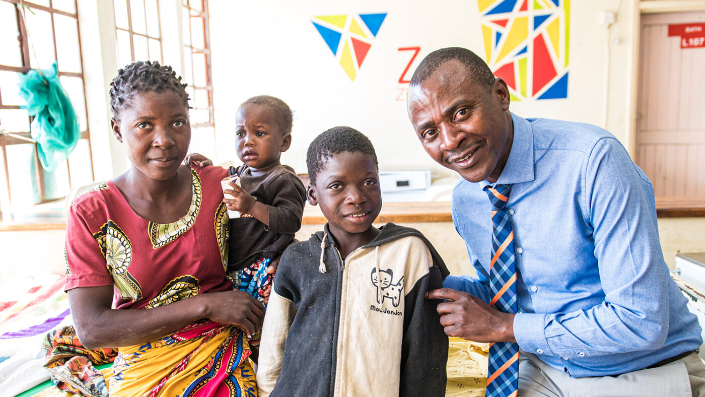 Dr Msukwa smiles while standing next to a young patient and his family.