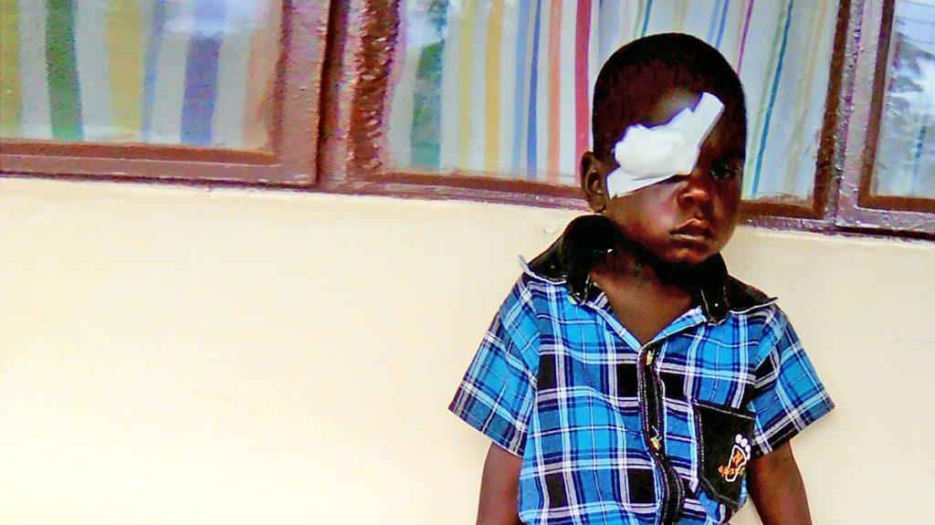 Zonobia sits with a bandage across her eye following her trachoma surgery.