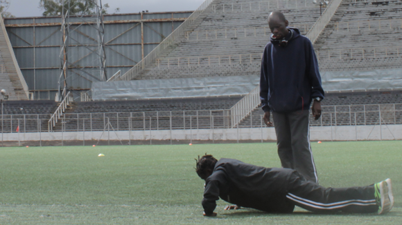 A coach training a young woman in an empty stadium.