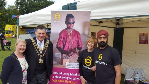 Two Lord Mayors and two Sightsavers volunteers standing together in front of a Sightsavers stall.