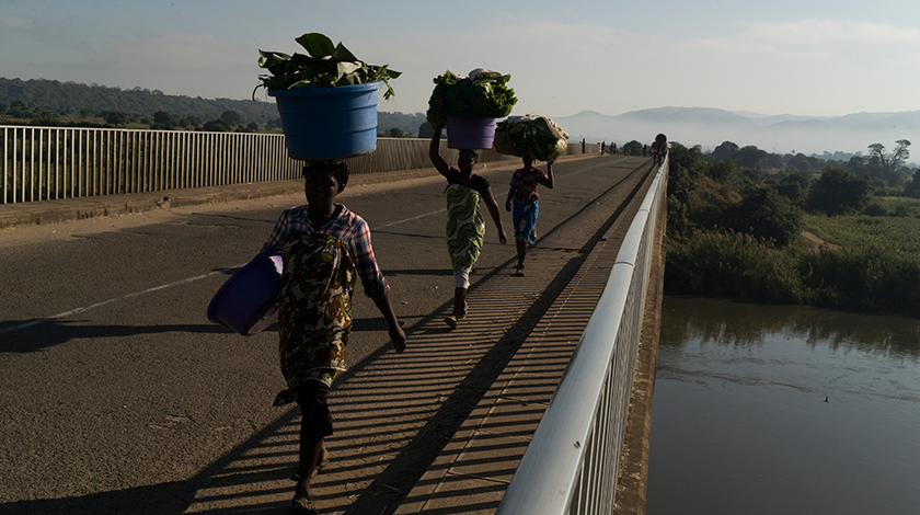 Three women walking across a bridge carrying large baskets on their heads.