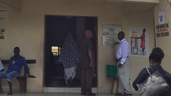 A women is walking up to the entrance of a building. Men stand around outside.