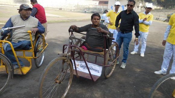 Mr Biharilal, who doesn't have legs, sitting in a tricycle.