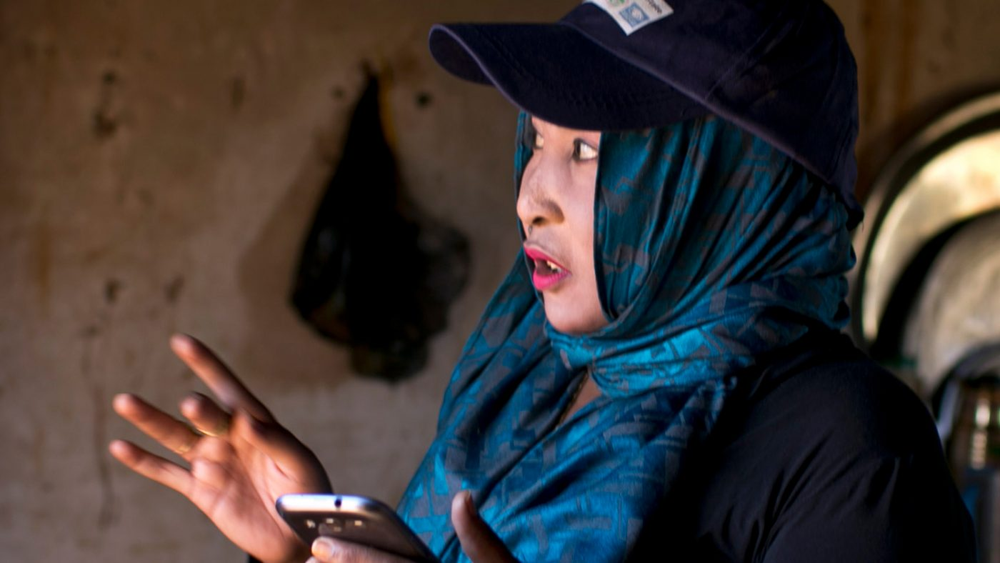 A woman collects data using a mobile phone.