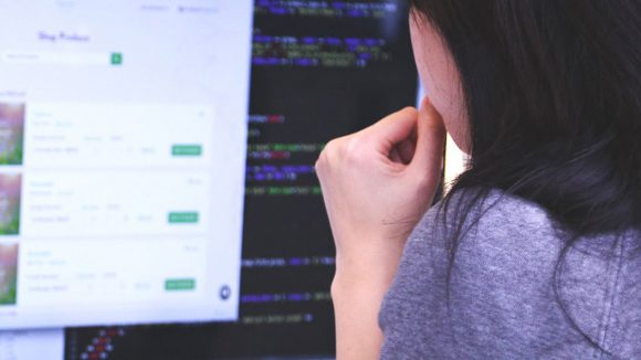 A woman sits at a desk looking at a computer screen.