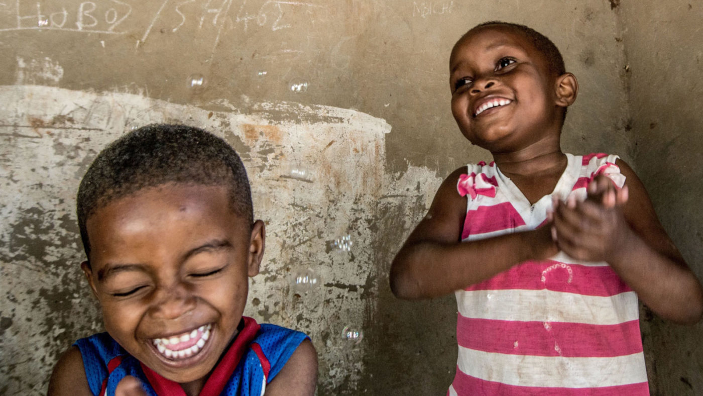 Asha and her brother play with bubbles, smiling and laughing.