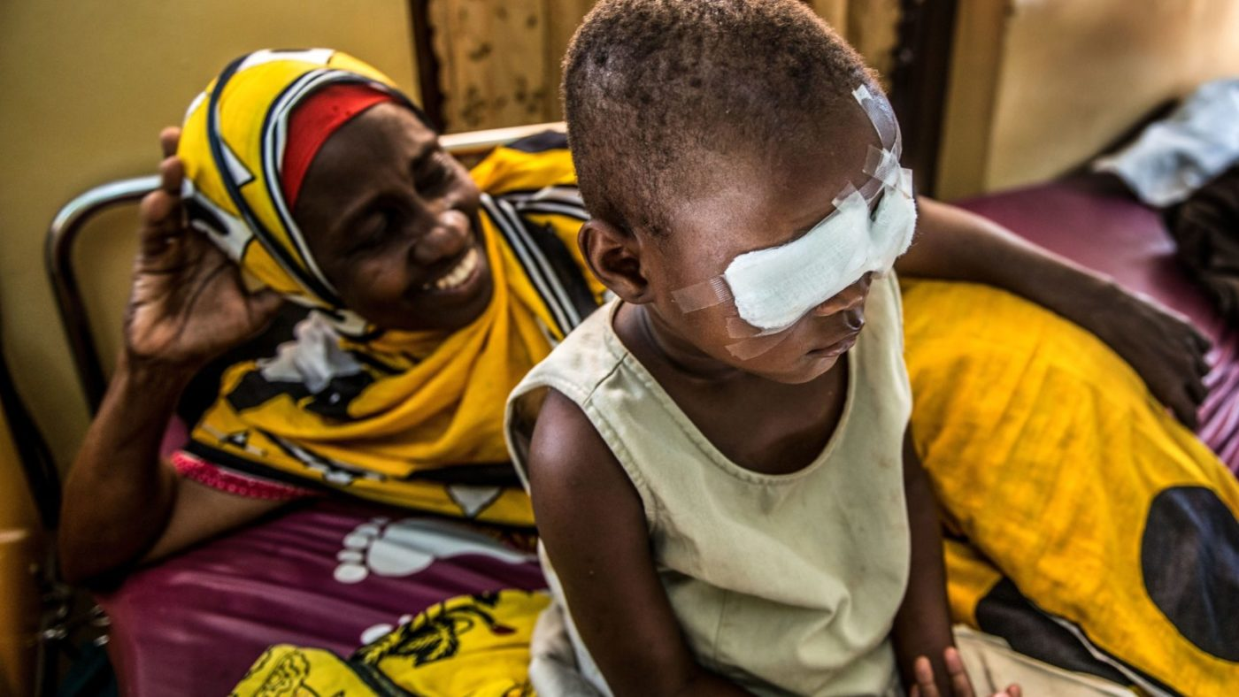Asha recovers in bed after her cataract surgery, accompanied by her guardian, Bimkubwa